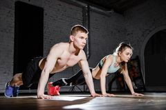 Fitness, sport, training, gym and lifestyle concept - young couple doing push-ups in the gym. Fitness, sport, training, gym and lifestyle concept - young couple stock image