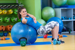 Fitness, sport, training, gym and lifestyle concept - young woman doing exercise on fitness ball Stock Photography