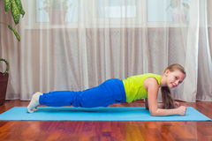 Fitness. sport, training and lifestyle concept - Child doing exercises on mat in home. Royalty Free Stock Photo