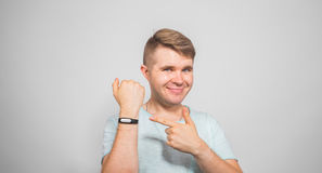 Fitness, sport, training and lifestyle concept - close up of young man with heart-rate watch bracelet studio shot on stock image