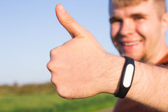 Fitness, sport, training and lifestyle concept - close up of young man with heart-rate watch bracelet in summer park. stock photography
