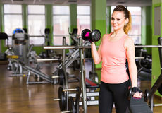 Fitness, sport, training and lifestyle concept - happy woman with dumbbells flexing muscles in gym Royalty Free Stock Photo