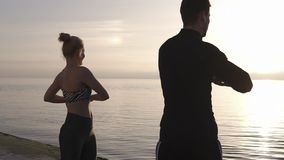 Fitness, sport, training and lifestyle concept - smiling couple stretching outdoors by the seaside in the morning. Sunrising light. Sports engaged woman and man stock video
