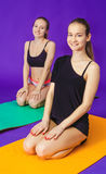 Fitness, sport, training and lifestyle concept - smiling two sporty women doing exercises on mat in gym Royalty Free Stock Photos