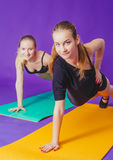 Fitness, sport, training and lifestyle concept - smiling two sporty women doing exercises on mat in gym Stock Image