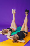 Fitness, sport, training and lifestyle concept - smiling two sporty women doing exercises on mat in gym Royalty Free Stock Images
