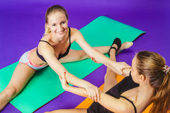 Fitness, sport, training and lifestyle concept - smiling two sporty women doing exercises on mat in gym Stock Photos