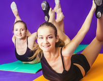 Fitness, sport, training and lifestyle concept - smiling two sporty women doing exercises on mat in gym Royalty Free Stock Photography