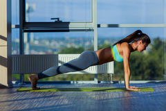 Fitness, sport, training and lifestyle concept - smiling woman stretching on mat in gym. light from a large window. Stock Images