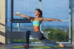 Fitness, sport, training and lifestyle concept - smiling woman stretching on mat in gym. light from a large window. Fitness, sport, training and lifestyle stock image
