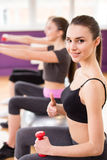Fitness. Sport, training and lifestyle concept - three smiling women with exercise balls and dumbbells in gym Royalty Free Stock Image