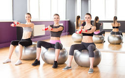 Fitness. Sport, training and lifestyle concept - three smiling women with exercise balls and dumbbells in gym Royalty Free Stock Photos