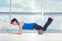 Fitness, sport, training and lifestyle concept - woman doing pilates on the floor with foam roller Stock Images