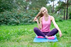 Fitness, sport, training, park and lifestyle concept - smiling woman doing exercises on mat outdoors.  Royalty Free Stock Photos