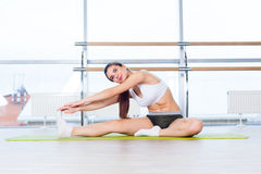 Fitness, sport, training and people concept -  Happy young woman stretching before running in gym Royalty Free Stock Images