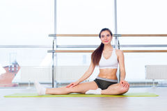 Fitness, sport, training and people concept -  Happy young woman stretching before running in gym Stock Images