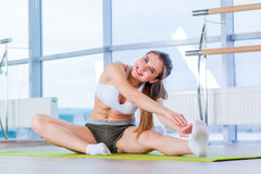 Fitness, sport, training and people concept -  Happy young woman stretching before running in gym Royalty Free Stock Image