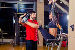 Fitness, sport, training and people concept - Personal trainer helping woman working with abdominal muscles press on the. Fitness, sport, training and people Royalty Free Stock Images