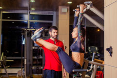 Fitness, sport, training and people concept - Personal trainer helping woman working with abdominal muscles press on the. Fitness, sport, training and people Royalty Free Stock Photography