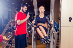 Fitness, sport, training and people concept - Personal trainer helping woman working with abdominal muscles press on the. Fitness, sport, training and people Stock Photography