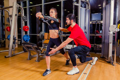 Fitness, sport, training and people concept - Personal trainer helping woman working with in gym. Fitness, sport, training and people concept - Personal trainer Stock Image