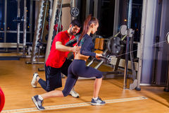 Fitness, sport, training and people concept - Personal trainer helping woman working with in gym Stock Photos