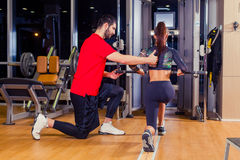 Fitness, sport, training and people concept - Personal trainer helping woman working with in gym. Fitness, sport, training and people concept - Personal trainer Stock Photography