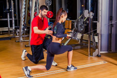 Fitness, sport, training and people concept - Personal trainer helping woman working with in gym. Fitness, sport, training and people concept - Personal trainer Royalty Free Stock Images