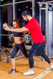 Fitness, sport, training and people concept - Personal trainer helping woman working with in gym Stock Photography