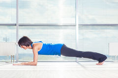 Fitness, sport, training and people concept - smiling woman doing abdominal exercises on mat in gym Royalty Free Stock Image