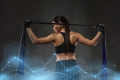 Woman with expander exercising in gym. Fitness, sport, training, people and lifestyle concept - woman doing exercises with expander or resistance band in gym Stock Photos