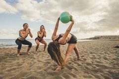 Fitness, sport, yoga and healthy lifestyle concept - group of people making pilates pose on beach. three young women doing royalty free stock photography