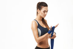 Fitness sportive girl winding elastic bandage over hand over white background. Royalty Free Stock Photo