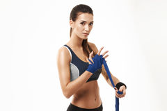 Fitness sportive girl winding elastic bandage over hand over white background. Copy space Royalty Free Stock Photography
