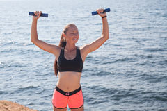 Fitness Sports girl trains muscles with dumbbells Royalty Free Stock Photo
