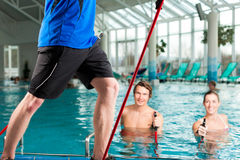 Fitness - sports gymnastics under water in swimming pool Royalty Free Stock Images