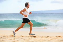 Fitness sports runner man jogging on beach. Handsome young fit sporty male athlete running outside on beautiful beach training. Caucasian male model in his 20s royalty free stock photos