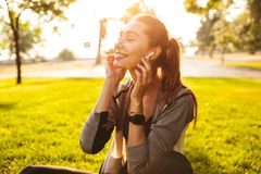 Fitness sports woman in park outdoors listening music with earphones. Stock Photos