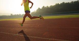 sportswoman running on sunrise track stock photo