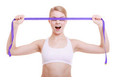 Fitness sporty girl covering her eyes with measuring tape isolated Royalty Free Stock Image