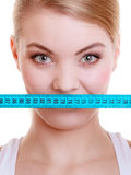 Fitness sporty girl covering her mouth with measuring tape isolated Stock Images