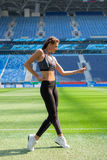 Fitness sporty girl in fashion sportswear and hip-hop dance at a football stadium, outdoor sports. Happy sexy woman having fun on Stock Photo