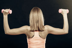Fitness sporty girl lifting weights back view Royalty Free Stock Photos