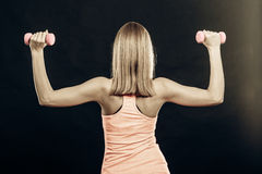 Fitness sporty girl lifting weights back view Stock Photography