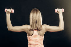 Fitness sporty girl lifting weights back view Stock Images