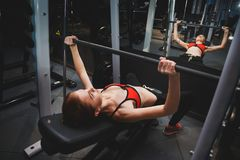 Fitness. Sporty woman exercising with barbell in gym Royalty Free Stock Images