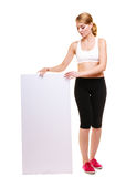 Fitness sporty woman holding blank empty ad banner. Fitness and health lifestyle advertisement. Young woman girl holding presenting blank empty banner ad Royalty Free Stock Photography