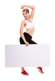 Fitness sporty woman holding blank empty ad banner. Fitness and health lifestyle advertisement. Young woman girl holding presenting blank empty banner ad Stock Photo