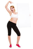 Fitness sporty woman holding blank empty ad banner. Fitness and health lifestyle advertisement. Young woman girl holding presenting pointing blank empty banner Stock Photography