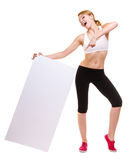 Fitness sporty woman holding blank empty ad banner. Fitness and health lifestyle advertisement. Young woman girl holding presenting pointing blank empty banner Stock Photo